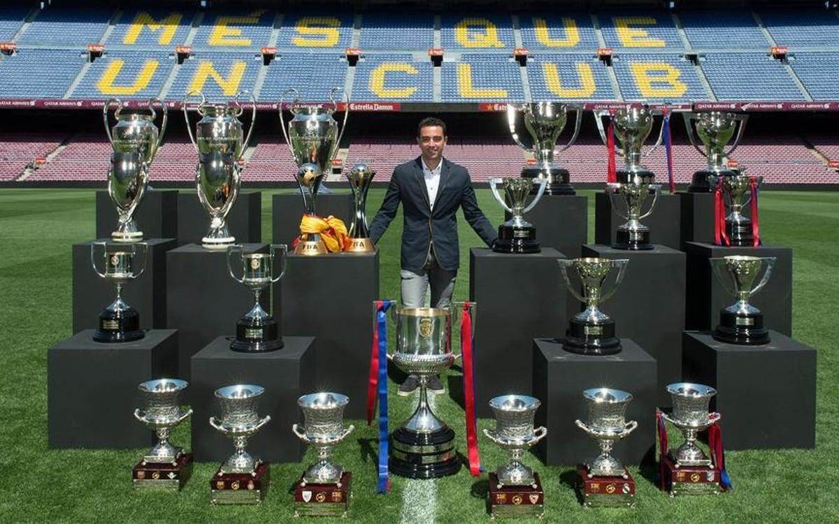 FCバルセロナで制覇した優勝杯とカンプノウで写真撮影を行うシャビ