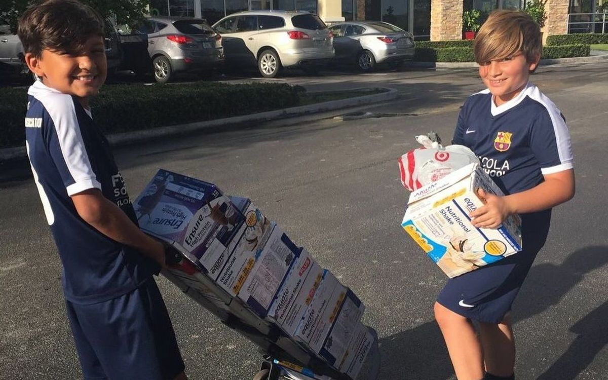 Two players from FCBEscola Florida arrange food collection for Puerto Rico